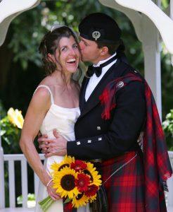 man in kilt kissing woman in wedding dress